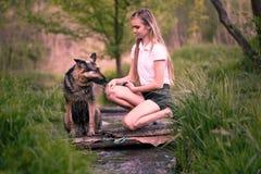 Adolescente con su perro que se sienta cerca de The Creek Imágenes de archivo libres de regalías
