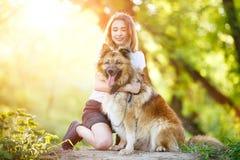 Adolescente con su perro que se sienta en parque Foto de archivo