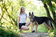 Adolescente con su perro que se sienta en parque Fotografía de archivo libre de regalías