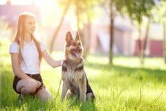 Adolescente con su perro que se sienta en parque Fotos de archivo