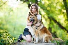 Adolescente con su perro que se sienta en parque Imagen de archivo