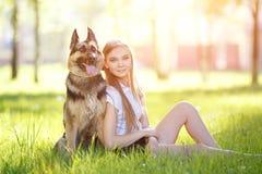 Adolescente con su perro que se sienta en parque Imagen de archivo libre de regalías