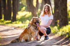 Adolescente con su perro que se sienta en parque Imagenes de archivo