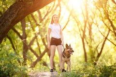 Adolescente con su perro que se sienta en parque Fotografía de archivo