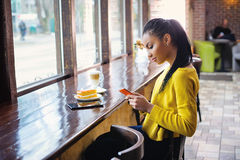 Adolescente con su teléfono celular en panadería Imagen de archivo