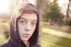 Adolescente con sudadera con capucha negra en un parque Foto de archivo libre de regalías