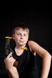 Adolescente con un arma y las flores Imagenes de archivo
