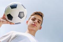 Adolescente con un balón de fútbol en a del cielo azul Fotografía de archivo libre de regalías