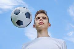 Adolescente con un balón de fútbol en a del cielo azul Foto de archivo libre de regalías