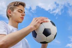 Adolescente con un balón de fútbol en a del cielo azul Imagenes de archivo