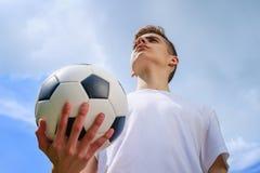 Adolescente con un balón de fútbol en a del cielo azul Imágenes de archivo libres de regalías