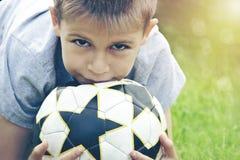 Adolescente con un balón de fútbol en sus manos contra la perspectiva del estadio tono Fotografía de archivo libre de regalías