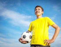 Adolescente con un balón de fútbol en un fondo del cielo azul Fotos de archivo