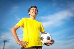 Adolescente con un balón de fútbol en un fondo del cielo azul Foto de archivo libre de regalías