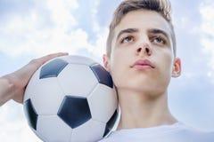 Adolescente con un balón de fútbol que juega en a del cielo azul Fotografía de archivo