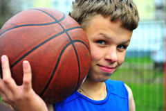 Adolescente con un baloncesto en la corte Fotografía de archivo libre de regalías