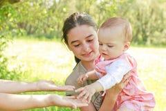 Adolescente con un bebé en sus brazos Fotografía de archivo