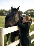 Adolescente con un caballo en un campo Imágenes de archivo libres de regalías