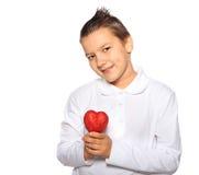 Adolescente con un corazón en sonrisas de las manos Foto de archivo