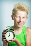 Adolescente con un despertador Foto de archivo