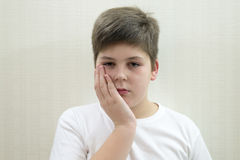 Adolescente con un dolor de muelas en fondo ligero Fotografía de archivo