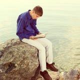 Adolescente con un libro al aire libre Imagenes de archivo