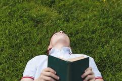 Adolescente con un libro en las manos que mienten en la hierba Fotografía de archivo libre de regalías