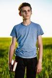 Adolescente con un libro en un campo de trigo Imágenes de archivo libres de regalías