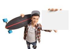 Adolescente con un longboard que muestra una tarjeta en blanco Imágenes de archivo libres de regalías