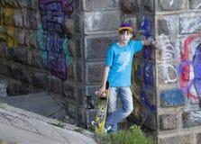 Adolescente con un monopatín Imagen de archivo libre de regalías