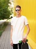 Adolescente con un monopatín Individuo fresco del inconformista en los vidrios de sol que presentan en un fondo borroso de la cal Imagenes de archivo