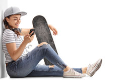 Adolescente con un monopatín que mira un teléfono Fotos de archivo