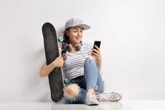 Adolescente con un monopatín usando un teléfono Imagenes de archivo