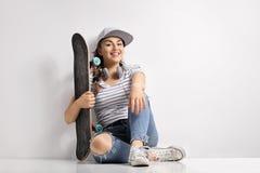 Adolescente con un monopatín y los auriculares Imagen de archivo libre de regalías