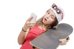 Adolescente con un monopatín y un teléfono Fotografía de archivo