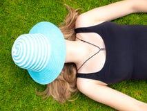 Adolescente con un sombrero que cubre su cara que miente en ella detrás Imagen de archivo libre de regalías