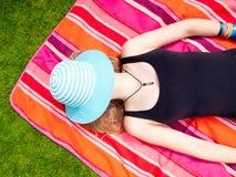 Adolescente con un sombrero que cubre su cara que miente en ella detrás Imágenes de archivo libres de regalías