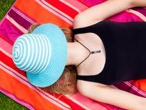 Adolescente con un sombrero que cubre su cara que miente en ella detrás Imagen de archivo