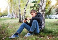 Adolescente con un teléfono al aire libre Foto de archivo libre de regalías