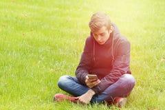 Adolescente con un teléfono en el parque Fotografía de archivo