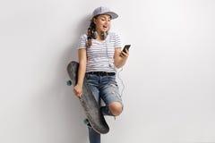 Adolescente con un teléfono y un monopatín Imagenes de archivo