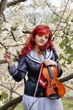 Adolescente con un violín en el jardín floreciente Foto de archivo libre de regalías