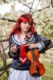Adolescente con un violín en el jardín floreciente Imagen de archivo