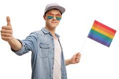 Adolescente con una bandiera ed i vetri dell'arcobaleno che fanno un pollice sul gestu Fotografie Stock