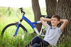 Adolescente con una bicicleta en el parque en la hierba Imagenes de archivo