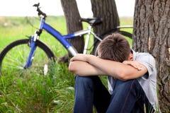 Adolescente con una bicicleta en el parque en la hierba Fotografía de archivo libre de regalías