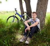 Adolescente con una bicicleta en el parque en la hierba Imágenes de archivo libres de regalías