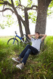 Adolescente con una bicicleta en el parque en la hierba Foto de archivo libre de regalías