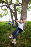 Adolescente con una bicicleta en el parque en la hierba Imagen de archivo libre de regalías