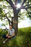 Adolescente con una bicicleta en el parque en la hierba Fotos de archivo libres de regalías